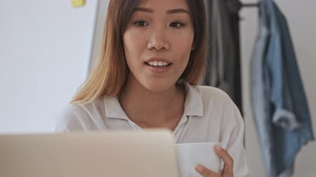 empregador : Calm asian business woman looking at the laptop while holding a cup of tea in the office