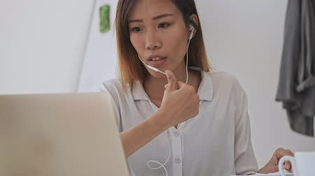 empregador : Calm asian business woman with wired headphones using a laptop while sitting by the table in the office