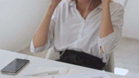 empregador : Happy asian business woman is having a phone call using her wired headphones while sitting at workplace Stock Footage
