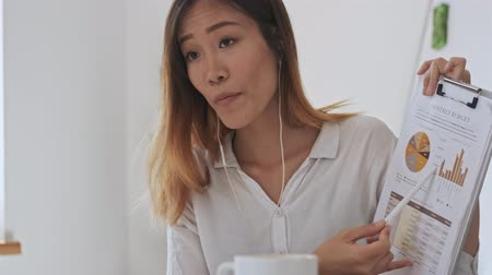 coreano : A serious asian business woman with wired headphones explaining and showing graphs and charts while having a video call on the laptop in white office Stock Footage