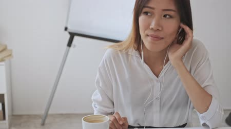 empregador : A beautiful asian business woman enjoying the music while using her wired headphones in the white office Stock Footage