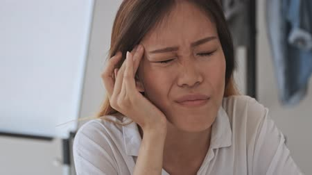 empregador : Tired asian business woman has a headache while sitting by the table in the office Stock Footage