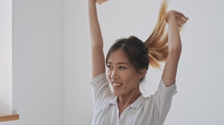 emelt : Good-looking asian business woman stretches while raising her hands in the white office