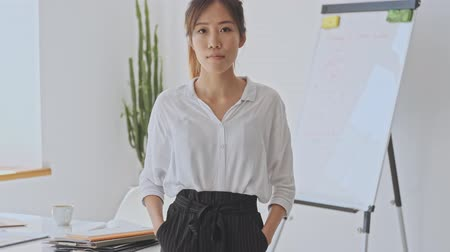 empregador : Beautiful calm young asian business woman stands in the white office while holding her hands in pockets