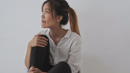 külső megjelenés : Pretty pensive young asian business woman sitting with a bent leg in the white office Stock mozgókép