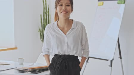 empregador : Pretty smiling asian business woman stands in the white office while holding her hands in pockets