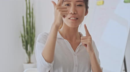 empregador : Positive joyful young asian business woman making a gun gesture in the white office