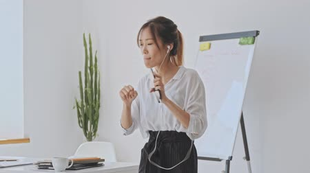empregador : Nice asian business woman dancing while listening to music using wired headphones in the white office Stock Footage