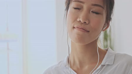 empregador : Crop view of asian young woman enjoy listening to music with closed eyes using wired headphones in the white office Stock Footage