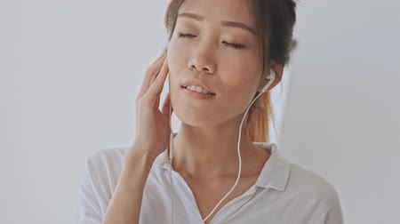 coreano : Charming asian young woman enjoy listening to music with closed eyes using wired headphones in the white office