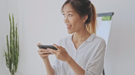 empregador : Smiling happy asian woman using a smartphone while holding it horizontally in the white office
