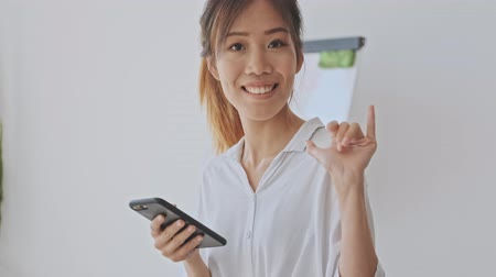 coreano : Pretty asian woman making a hello gesture while waving her hand in the white office Stock Footage