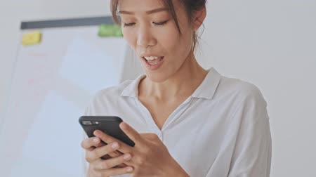 empregador : Pretty asian woman browsing in her smartphone while waiting for someone then looking to the side in the white office