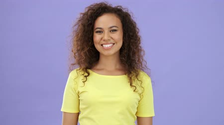 violet color : Happy african young woman in yellow t-shirt smiling while looking at the camera over purple background isolated