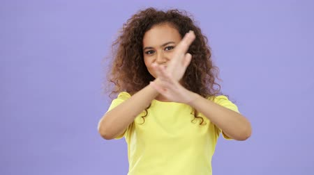 armen over elkaar : Beautiful african young woman in yellow t-shirt crossing her arms and showing no sign with hands while looking at the camera over purple background isolated