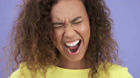 camiseta : Close up view of angry pretty african young woman in yellow t-shirt screaming while looking at the camera over purple background isolated Stock Footage