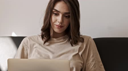 tuvalet : Smiling concentrated brunette woman using laptop computer while sitting on sofa indoors