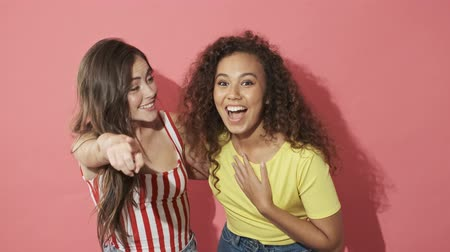 adorável : Two cheerful pretty girls friends becoming happy and pointing at the camera over pink background Stock Footage