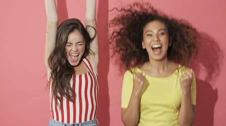 adorável : Two cheerful intrigued pretty girls friends experiencing excitement and becoming happy after that while pointing at the camera over pink background
