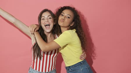 adorável : Two happy pretty girls friends having fun together and looking at the camera over pink background Stock Footage