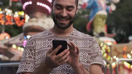 szórakoztatás : A smiling handsome man is using his smartphone outdoors in amusement park