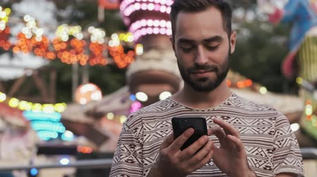 szórakoztatás : A positive attractive man is using his smartphone outdoors in an amusement park