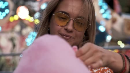 karneval : An attractive woman is eating a big pink candyfloss in the amusement park Dostupné videozáznamy