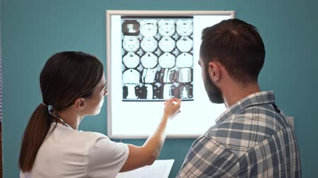 computed : A female doctor in medical uniform is showing an x-ray scan computed tomography results to sick patient man in hospital Stock Footage