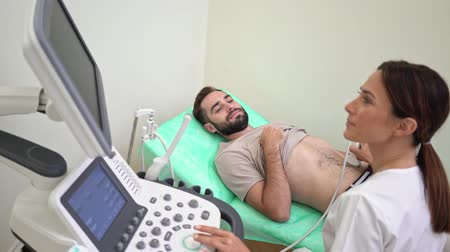 computed : An attractive man is getting abdominal ultrasound scan by female doctor in medical uniform at hospital Stock Footage