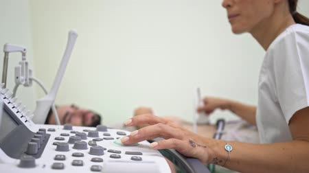 computed : A close-up view of female doctor in medical uniform is doing abdominal ultrasound scan for young lying man at hospital Stock Footage