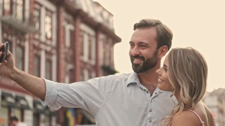 make photo : Nice smiling young couple man and woman are taking a selfie on the smartphone at the city street in summer