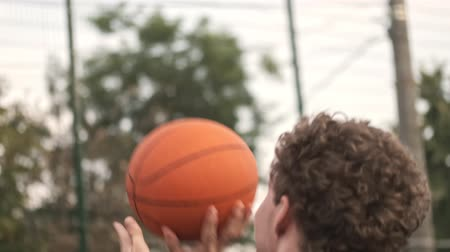поражение : Back view of curly handsome man playing basketball on basketball court outdoors