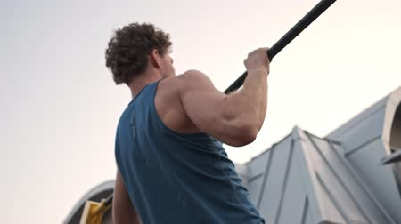 sportowiec : Focused young curly man doing sports exercise horizontal bar outdoors