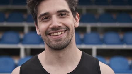plac zabaw : Close up view of cheerful handsome man looking at the camera and becoming happy on stadium outdoors