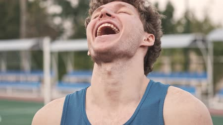 закрытыми глазами : Close up view of cheerful curly handsome man looking at the camera while laughing with open mouth and closed eyes on stadium outdoors