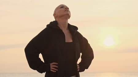 закрытыми глазами : Focused attractive bald sports woman warming up her neck with closed eyes near the sea outdoors