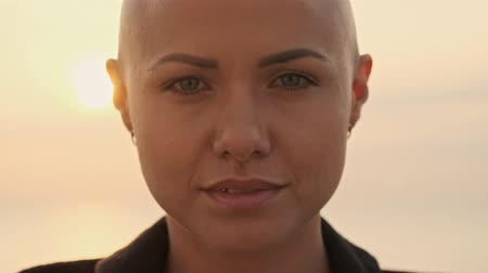 boa aparência : Close up view of Young attractive bald sports woman becoming happy and looking at the camera near the sea outdoors Stock Footage