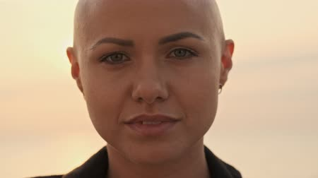 shy girl : Close up view of Young attractive bald sports woman becoming happy and looking around near the sea outdoors Stock Footage