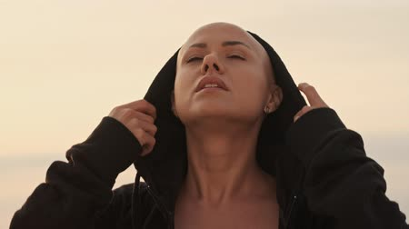 ciddi : Mystery attractive bald sports woman putting on a hood and looking away while standing near the sea outdoors Stok Video