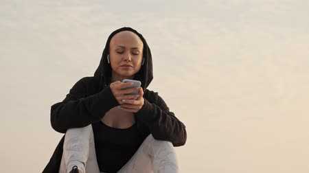 aşağıda : Smiling attractive bald sports woman in hood and earphones using smartphone while sitting near the sea outdoors Stok Video