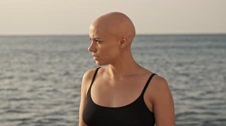 tajemnica : Serious attractive bald sports woman looking away while standing near the sea outdoors