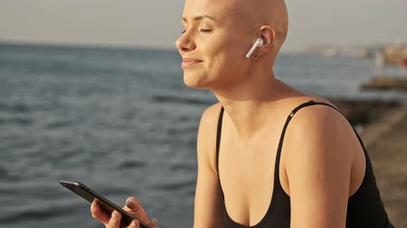 incecik : Pleased attractive bald sports woman in earphones listening music with closed eyes and holding smartphone near the sea outdoors Stok Video