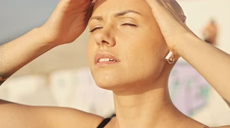 incecik : Close up view of Pleased attractive bald sports woman in earphones listening music with closed eyes and basking in the sun while sitting near the sea outdoors Stok Video