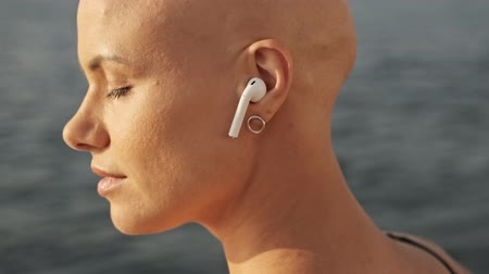 закрытыми глазами : Side view of Pleased attractive bald sports woman in earphones listening music with closed eyes while sitting near the sea outdoors Стоковые видеозаписи
