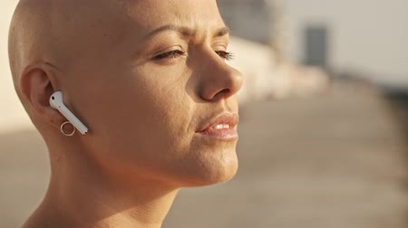 закрытыми глазами : Close up view of Pleased attractive bald sports woman in earphones listening music with closed eyes and enjoying this moment while sitting near the sea outdoors Стоковые видеозаписи