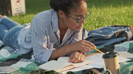 campus universitario : Concentrated pretty african woman in eyeglasses studying with book while lying on plaid in the park Archivo de Video