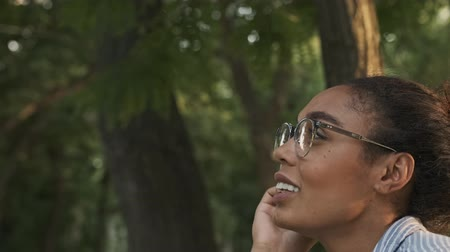 campus universitario : Side view of Cheerful pretty african woman in eyeglasses looking away while sitting in the park