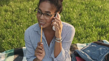 campus universitario : Happy pretty african woman in eyeglasses talking by smartphone with pencil in hand while sitting in the park Archivo de Video