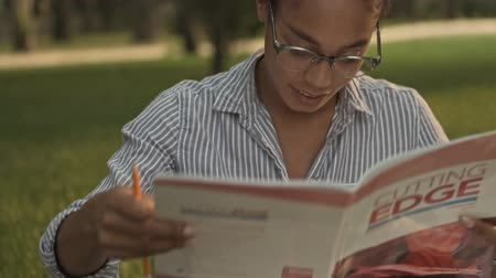 campus universitario : Happy pretty african woman in eyeglasses studying with magazine and book while sitting in the park