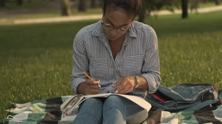 excluir : Happy pretty african woman in eyeglasses studying with magazine and writing something while sitting in the park